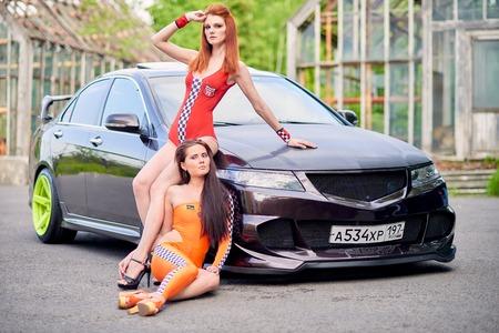 Moscow. Russia. May 26, 2015. Two beautiful girls next to a racing, sports car. Foto de archivo - 104748914