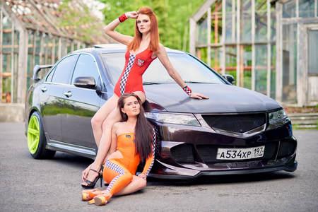 Moscow. Russia. May 26, 2015. Two beautiful girls next to a racing, sports car. Foto de archivo - 104748915