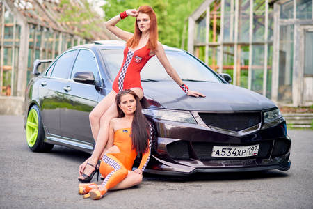 Moscow. Russia. May 26, 2015. Two beautiful girls next to a racing, sports car. Foto de archivo - 104748916