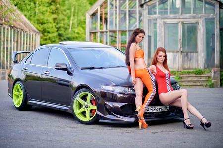 Moscow. Russia. May 26, 2015. Two beautiful girls next to a racing, sports car. Foto de archivo - 104748919