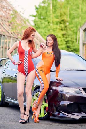 Moscow. Russia. May 26, 2015. Two beautiful girls next to a racing, sports car. Foto de archivo - 104748923