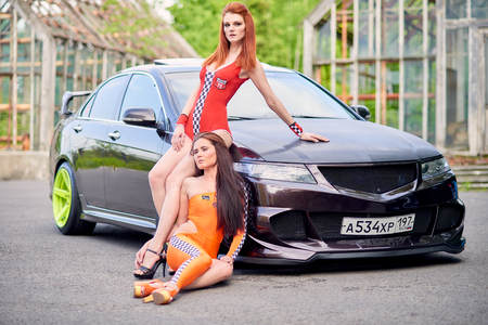 Moscow. Russia. May 26, 2015. Two beautiful girls next to a racing, sports car. Foto de archivo - 104748927