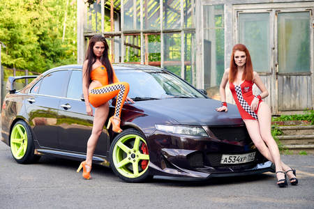 Moscow. Russia. May 26, 2015. Two beautiful girls next to a racing, sports car. Foto de archivo - 104748930