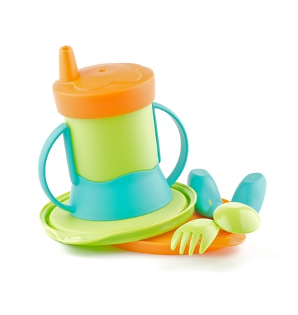 Botella coloreada multi del bebé y el bebé utensilio aislado sobre fondo blanco