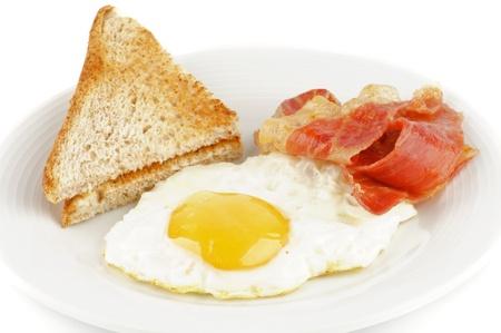 Tocino, huevos y tostadas aisladas sobre fondo blanco Foto de archivo