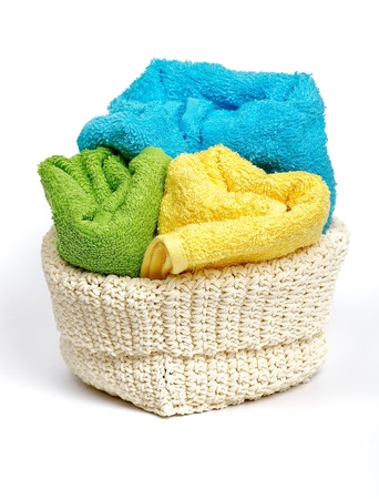 Multi-colored Terry towels in wattled container isolated on white background photo