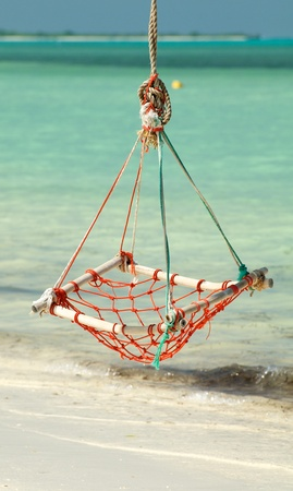Hammock Rope Swing in tropical environment on ocean beach background photo