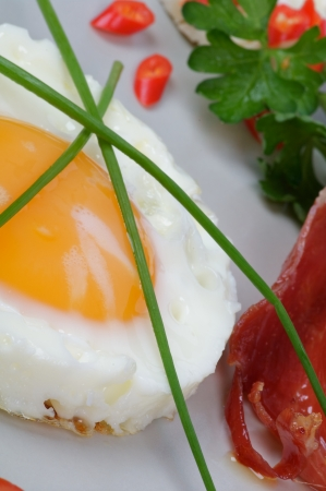 Fried Eggs Sunny Side Up with Lettuce and bacon closeup on gray plate photo