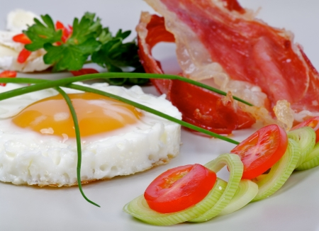 Fried Eggs Sunny Side Up with Bacon, Lettuce and vegetables closeup on gray plate photo