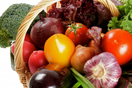 close up of onions in a basket: Basket of Various Vegetables with Broccoli, radishes, lettuce, onions, leeks, beets, carrots, red tomatoes, yellow tomatoes, parsley close up Stock Photo