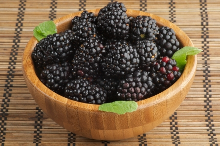 Perfect Ripe Blackberries in Wooden Bowl isolated on Strawmat background Stock Photo - 14769546