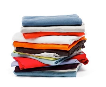 Stapel von Farbe T-Shirts und Kleidung isoliert auf weißem Hintergrund