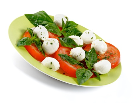 Italian Caprese Salad with Basil, Fresh Mozzarella, Tomatoes and Olive Oil on green plate isolated on white background Reklamní fotografie
