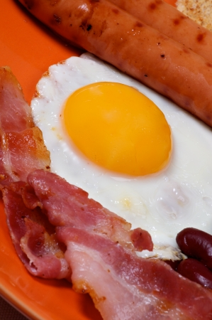 English Breakfast with Sausage, Bacon, Fried Eggs Sunny Side up and  Beans, close up on orange plate  Focus on Egg Yolk. Stock Photo