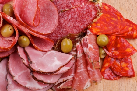 Arrangement of Meat delicatessen with Ham, Pepperoni, Chorizo and Olives close up on wooden backgound Stock Photo - 15048680