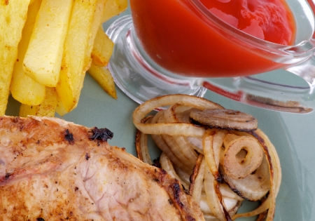 Unhealthy Lunch with Pork Steak, French Fries, Grilled Onion and Ketchup close up on green plate photo