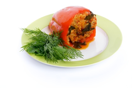 Homemade Red Bell Pepper Filled with Rice, Meat, Onion and Parsley on green plate isolated on white background photo