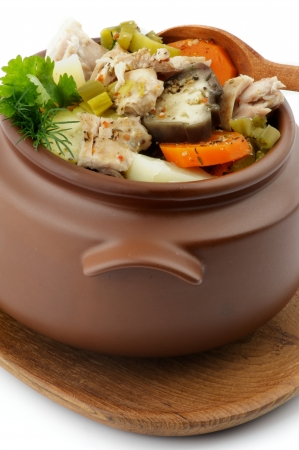 Chicken Stew, Vegetables and Greens in Brown Pot with Wooden Spoon isolated on white background