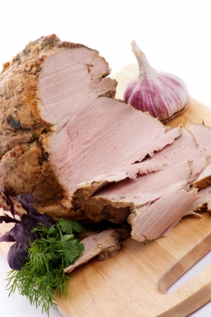 Pork Roast and Slices on Cutting Board with Greens and Garlic close up Stock Photo - 15609036