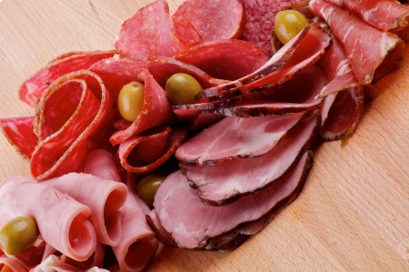 prosciutto: Slices of Delicatessen with Ham, Pepperoni, Chorizo and Olives closeup on Cutting Board
