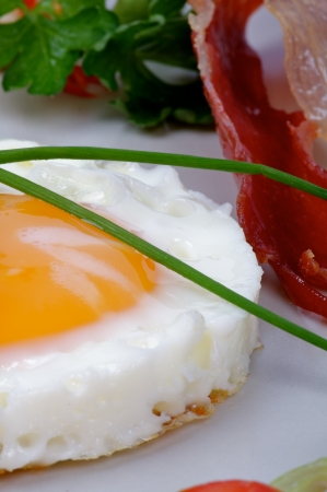 Fried Eggs Sunny Side Up with Lettuce, Greens and Roasted Bacon closeup on Gray Plate photo