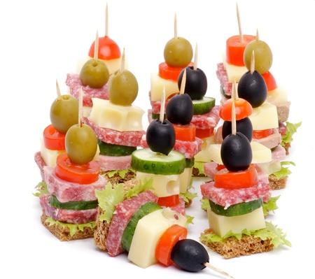 Anordnung Canape mit Bacon, Salami, Tomaten, Käse, Gurken, grüne Olive, Black Olive, Salat und Vollkornbrot isoliert auf weißem Hintergrund