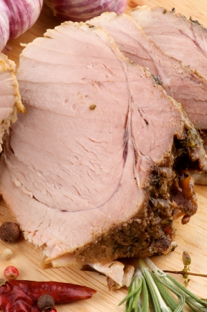 Slices of Juicy Roasted Pork with Spices, Rosemary and Garlic closeup on Cutting Board Stock Photo - 15908306