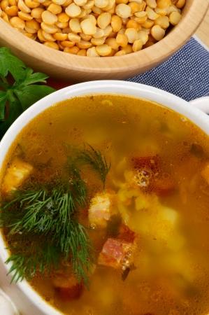 Erbsensuppe mit Kartoffeln und geräucherter Schinken in Bowl Nahaufnahme auf Yelow Peas Bowl Hintergrund