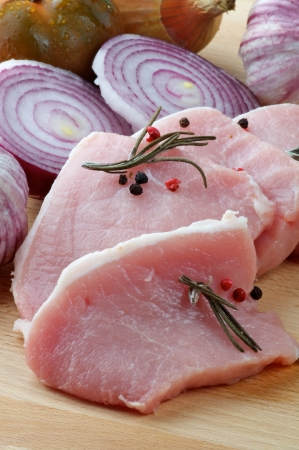 Arrangement of Raw Pork Loin Chops with Rosemary, Peppercorn and Onions on Wood Cutting Board closeup Stock Photo - 16748607