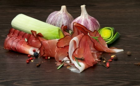 Arrangement of Thin Slices of Jamon, Garlic, Leek and Spices close up on Dark Wood background Stock Photo - 16806719