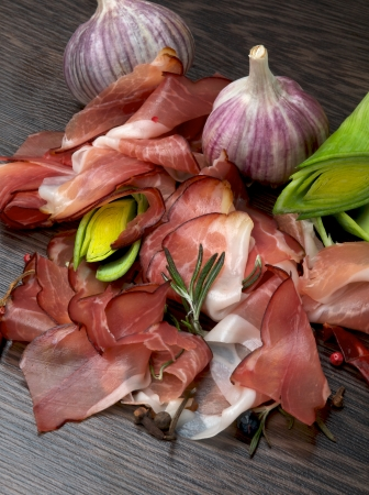 Arrangement of Jamon, Leek, Garlic and Spices on Dark Wood background Stock Photo - 16806799