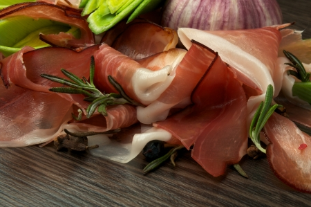 Slices of Perfect Jamon, Leek, and Garlic closeup on Dark Wood background Stock Photo - 16906328