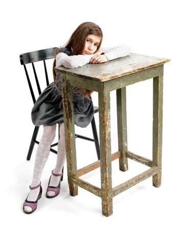 Sad Girl Sitting on Chair and Leaning on Big Table closeup on white background photo