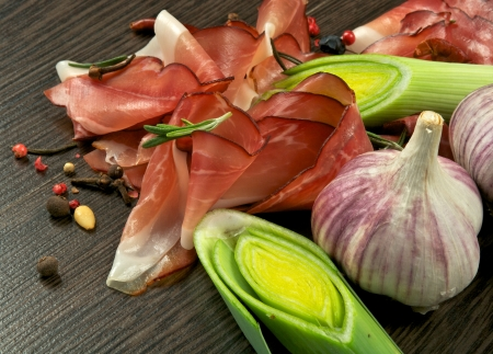 Arrangement of Jamon Slices, Ripe Leek, Garlic, Peppercorn and Rosemary closeup on Dark Wood background Stock Photo - 16948822