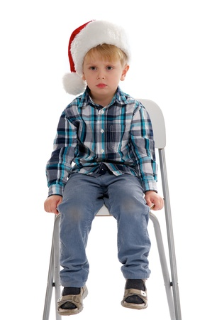 Little Boy with Santa Hat Sitting on Chair and Asking  photo