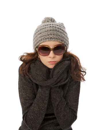 Beautiful Girl in Knitted Hat, Warm Sweater and Sunglasses Shiver with Cold  closeup on white background photo
