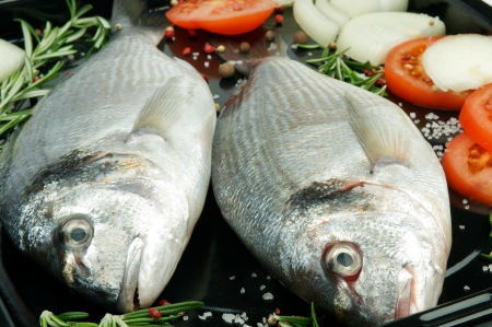 Two Fresh Gilthead Fish with Onion, Tomatoes, Spices and Rosemary on Black Dripping Pan prepared to frying Stock Photo - 17010933