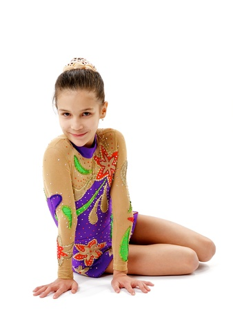 relaxes: Young Girl Gymnast Relaxes after Successful Exercising and Smiling Pleased face on white background Stock Photo