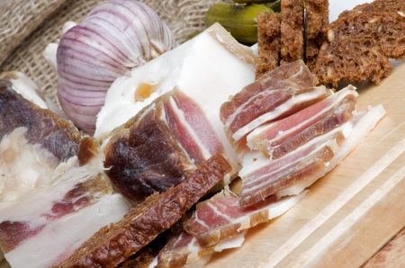 uncooked bacon: Raw Smoked Homemade Bacon Full Body and Slices with Garlic, Brown Bread and Gherkins closeup on Cutting Board