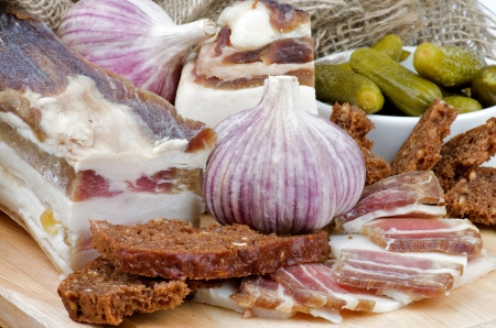 Arrangement of Raw Smoked Homemade Bacon, Garlic, Brown Bread and Gherkins closeup on Cutting Board Stock Photo - 17174314