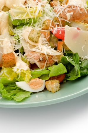 Caesar Salad with Grilled Chicken Breast, Garlic Crouton, Romaine Lettuce, Cherry Tomato, Eggs, Sauce and Grated Parmesan Cheese closeup on Green Plate photo