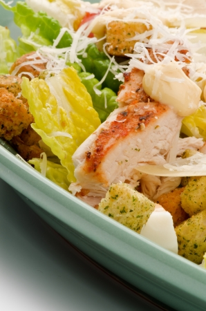 Caesar Salad with Grilled Chicken, Crouton, Romaine Lettuce,  Sauce and Grated Parmesan Cheese closeup on Green Plate photo