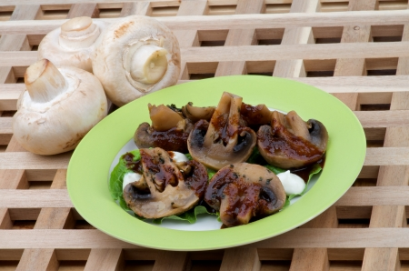 sause: Perfect Grilled Mushrooms Champignons with Grill Sause, Lettuce and Sour Cream on Green Plate closeup on Wood background and Raw Mushrooms