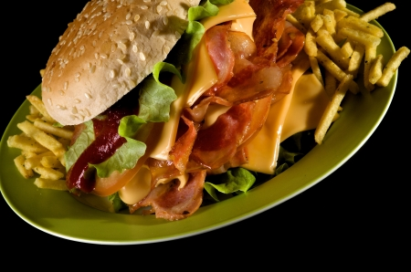 comida chatarra: Big Burger sabrosa con tocino a la parrilla, queso, lechuga, tomate y papas fritas en blanco placa verde sobre fondo negro