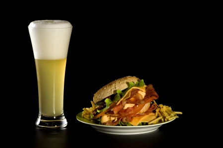 White Beer Glass, Big Burger  with Bacon, Cheese, Lettuce and French Fries isolated on black background photo