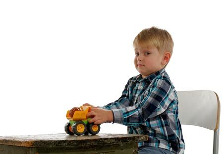 Niño pequeño se sienta en la silla, juega con sus coches de juguete y dice: