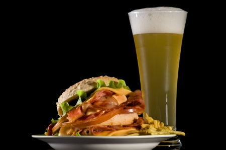 Big Burger with Bacon, Cheese, Lettuce French Fries Wheat Beer Glass iolated on black background photo
