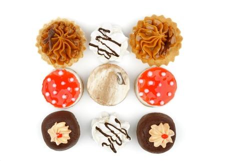 Disposición de las magdalenas de chocolate, tartaleta, Strawberry Cheesecake Jelly Dot Polka y merengue de chocolate negro esmaltado aislado en blanco Vista superior de fondo