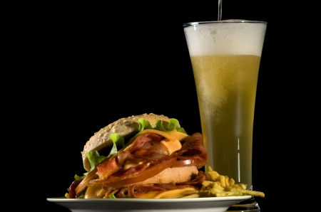 Spilling Glass of Beer and Big Tasty Burger with Fried Bacon, Lettuce, Tomato, Cheese and French Fries isolated on black background photo