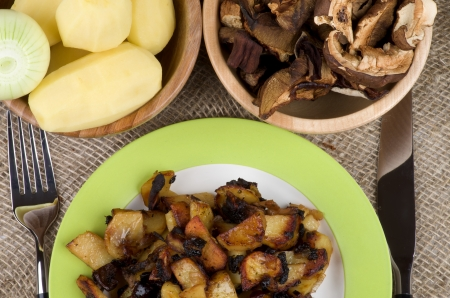 prepared potato: Traditional Roasted Potato with Mushrooms, Onion and Spices  Arrangement of Green Plate with Prepared Potato, Two Wood Bowls with RawPotato, Onion and Slices of Mushrooms and Fork with Knife close up